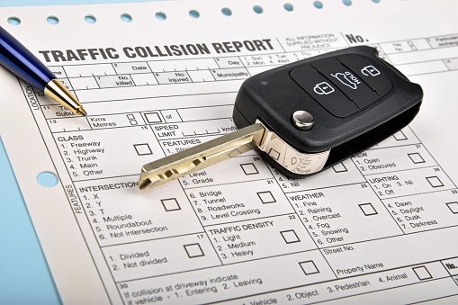 Car key on top of accident report